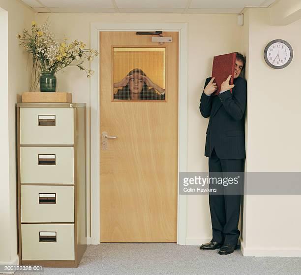 Man in office hiding from woman peering through window in door