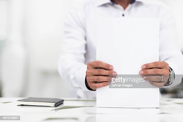 Man in office holding papers, Stockholm, Sweden