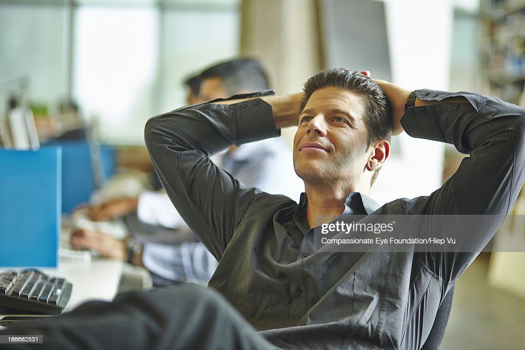Man in office leaning back in chair : Stock Photo