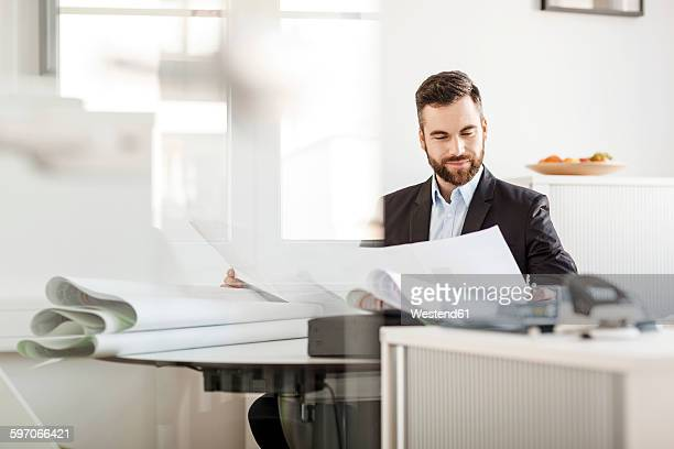 Man in office looking at construction plan