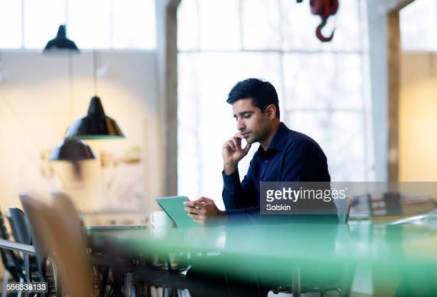 Man in office, looking at tablet