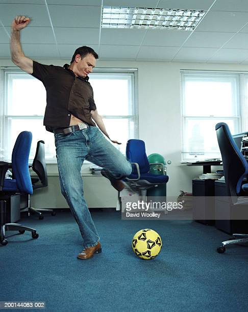 Man in office preparing to strike football, low angle view