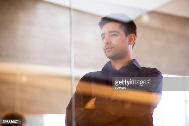 Man in office, standing behind glas wall