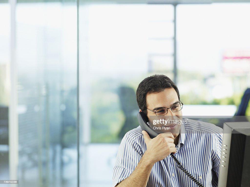 Man in office talking on telephone : Stock Photo