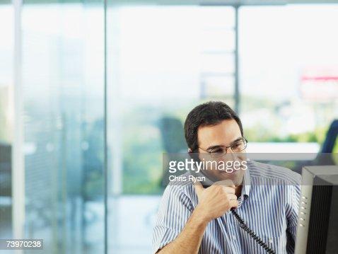 Uomo in ufficio a parlare sul telefono