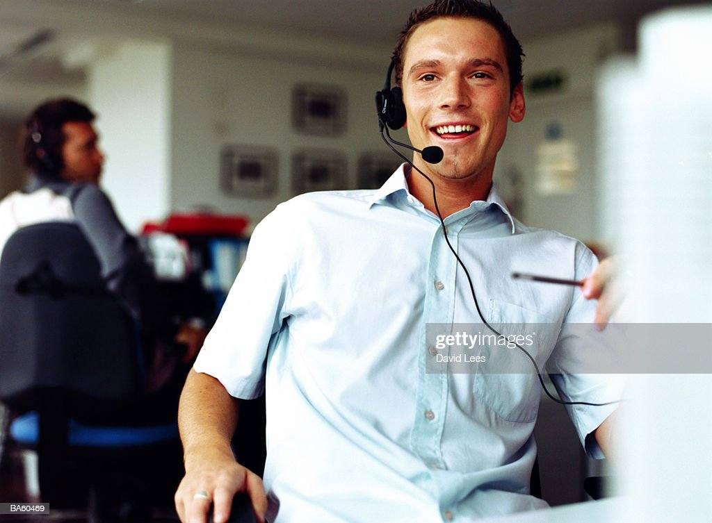 Man in office wearing headset, close-up : Stock Photo