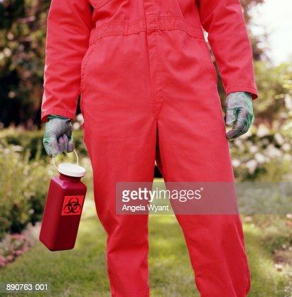 Man in orange overalls carrying bio hazard container in garden
