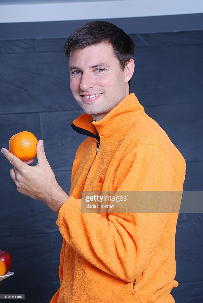 Man in orange shirt holding and orange with left hand looking at camera
