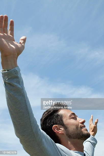 Man in outdoors with arms outstretched and eyes closed