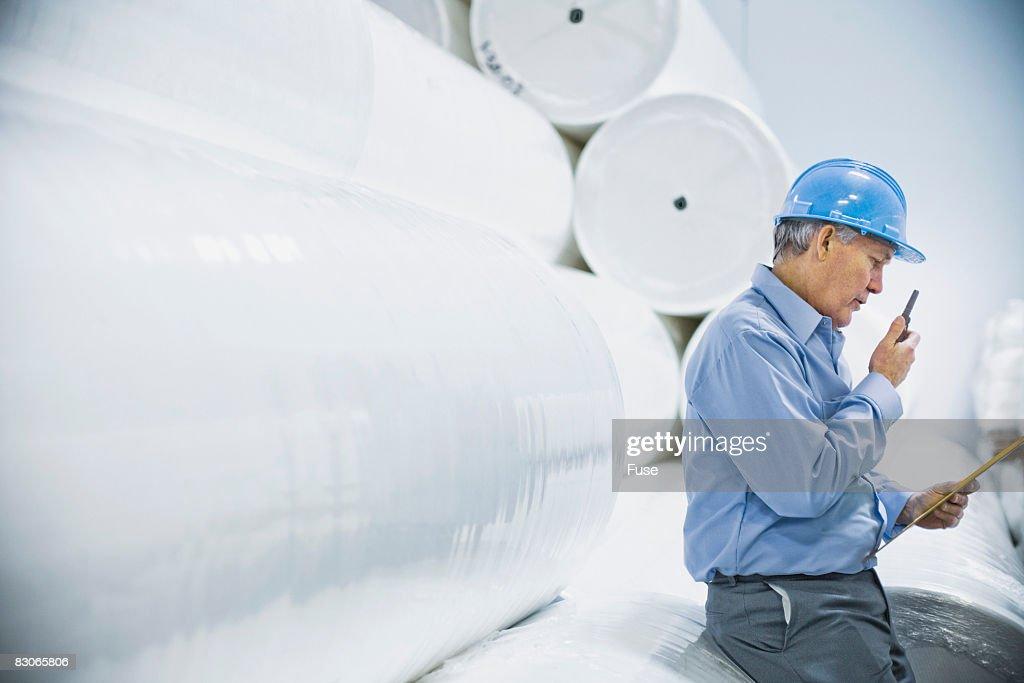 Man in Paper Mill Talking on Walkie-Talkie