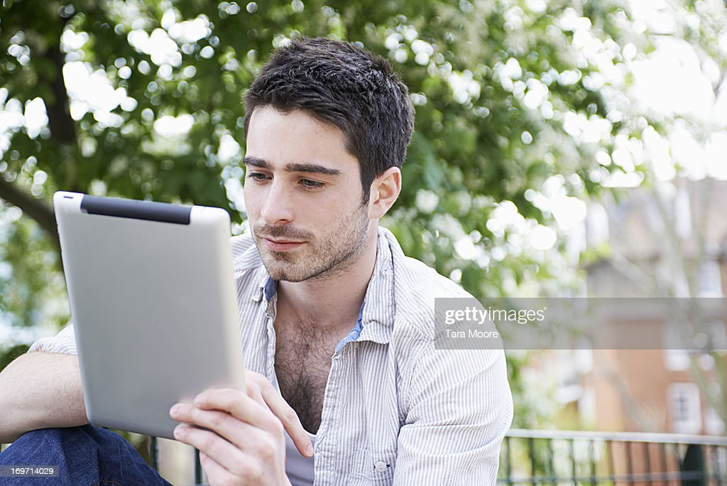 man in park looking at digital tablet : Stock Photo