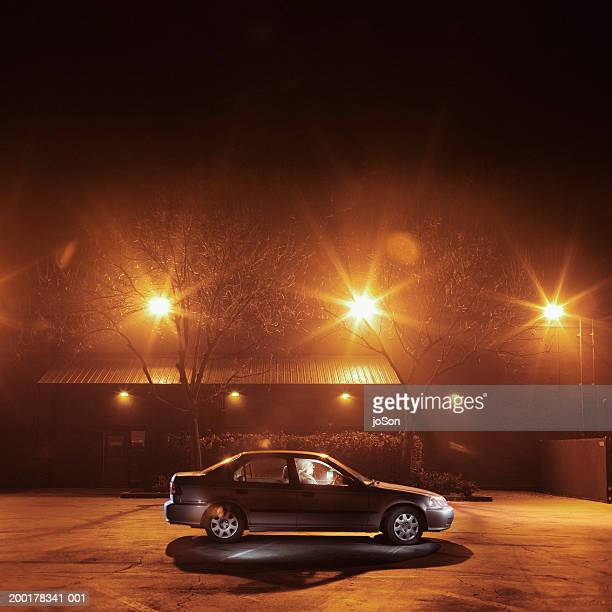 Man in parked car, night, side view (long exposure)