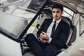 Young handsome businessman is sitting in private plane. Confident and successful man in airport.