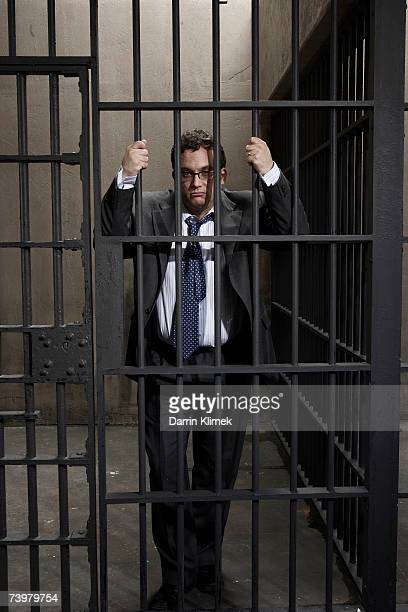 Man in prison cell, holding bars, portrait
