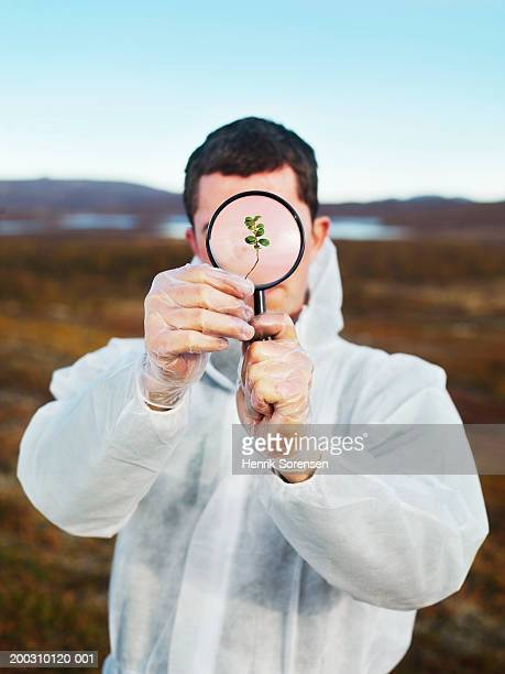 Man in protective suit looking at plant through magnifying glass