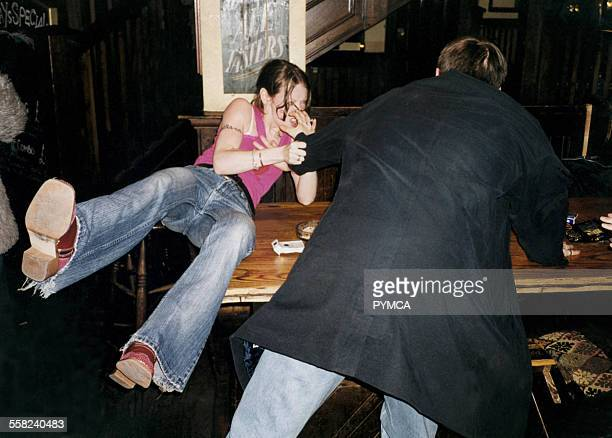 Man in pub splits up fight bewteen his wife and another woman by pushing one of them over a table Kent UK 2000s