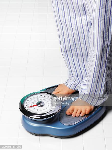 Man in pyjamas standing on weighing scales in bathroom, low section