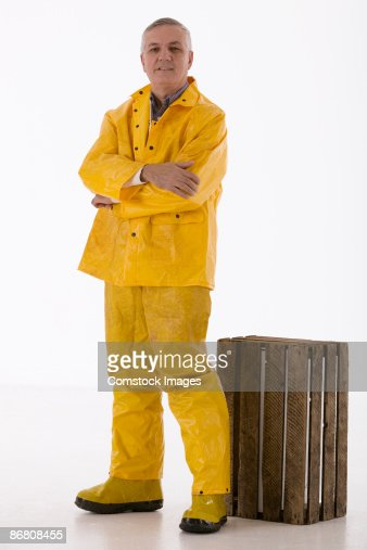 Man in rain gear with wooden crate