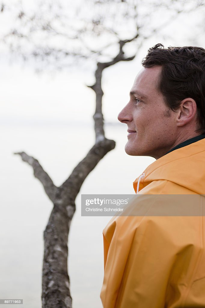 man in raincoat looking on a lake : Stock Photo