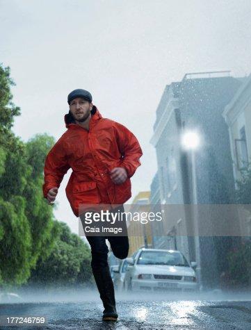 Man in raincoat running in rain