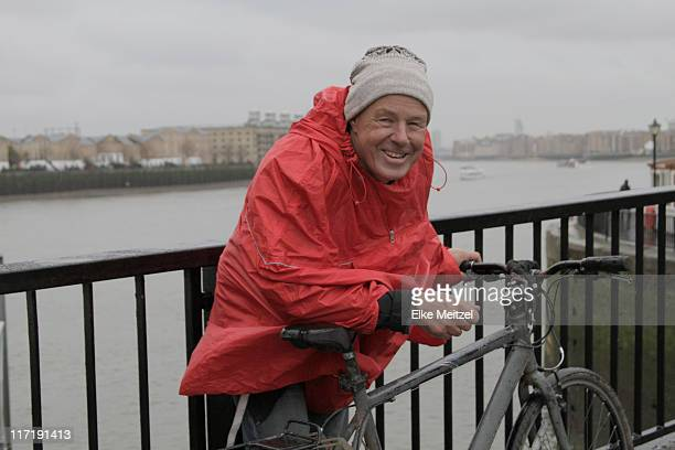 Man in raincoat with pushbike