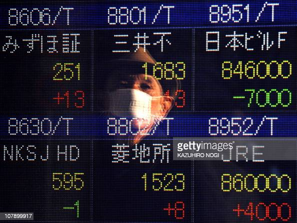 A man in reflection looks at an electronic quotation boad in Tokyo on January 6 2011 Japanese shares surged 144 percent to end at a new eightmonth...