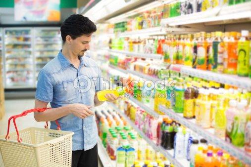 Hombre en supermercado adquirir una botella de jugo : Foto de stock