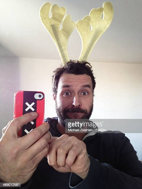 Man in reindeer head decoration clicking himself with camera phone