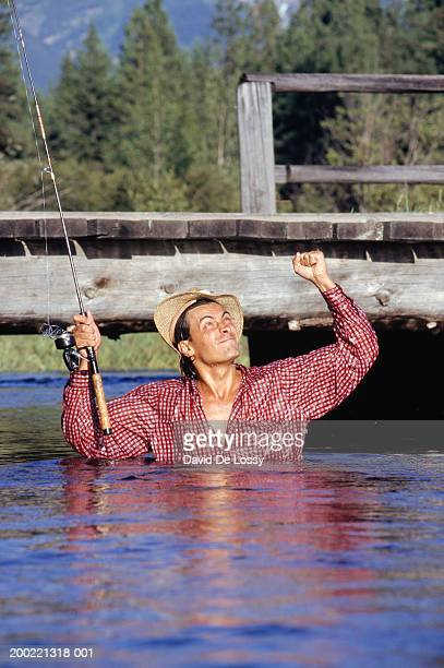 Man in river up to chest, with fishing rod