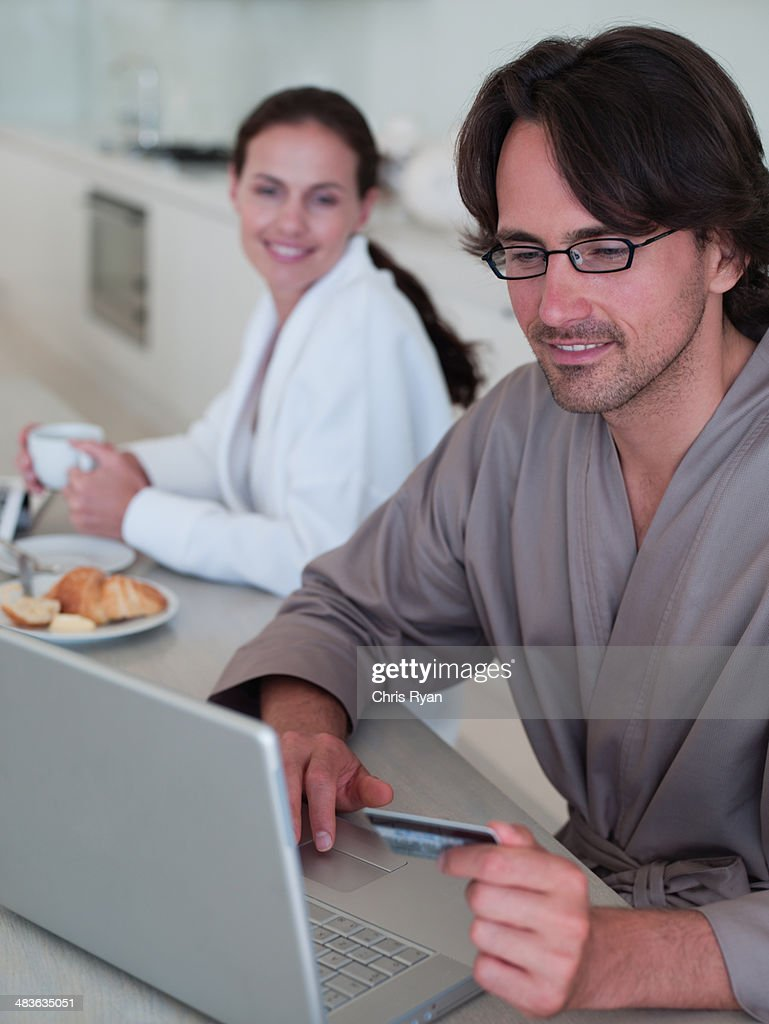 Man in robe with eyeglasses sitting with laptop and woman in background : Stock Photo