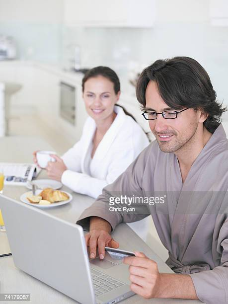 Man in robe with eyeglasses sitting with laptop and woman in background