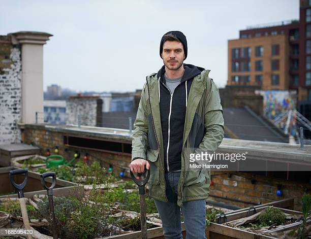 Man in roof garden holding spade, wearing coat.