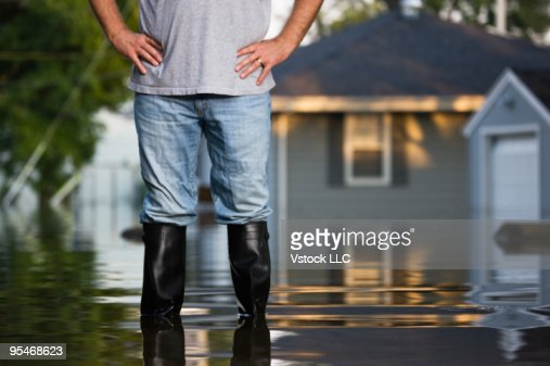 Man in rubber boots during flood