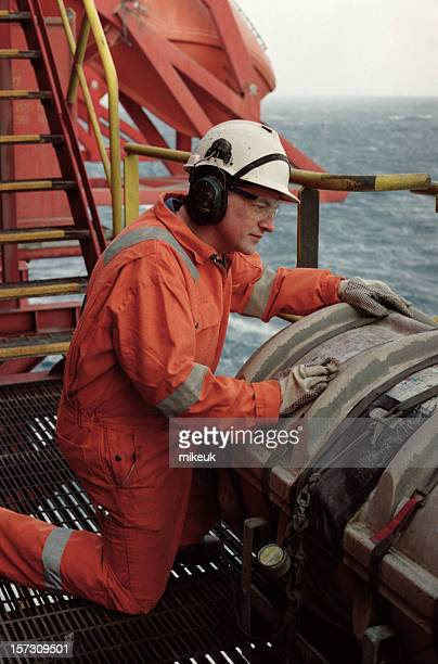 A man in safety gear working on a oil rig