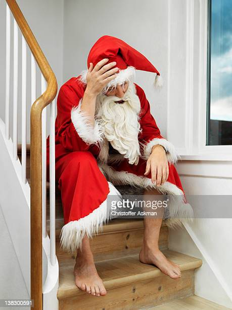 Man in Santa Claus suit sitting on steps