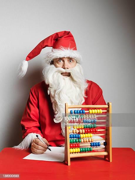 Man in Santa Claus suit using abacus