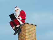 Man in santa suit sitting on chimney, using laptop, low angle view
