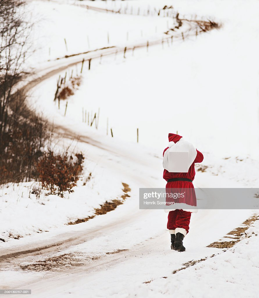 Man in santa suit with sack over shoulder on snowy lane, rear view : Stock Photo