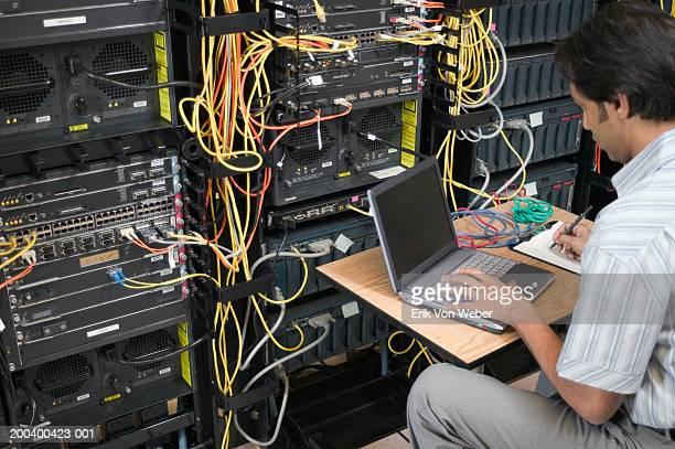 Man in server room using laptop