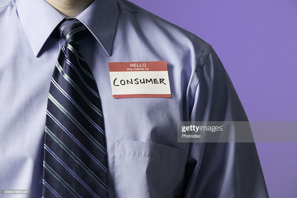 Man in shirt and tie with introduction sticker on chest saying consumer, mid section : Stock Photo