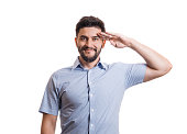 Portrait of handsome man. Young black haired guy with facial hair in blue casual shirt saluting with hand at forehead