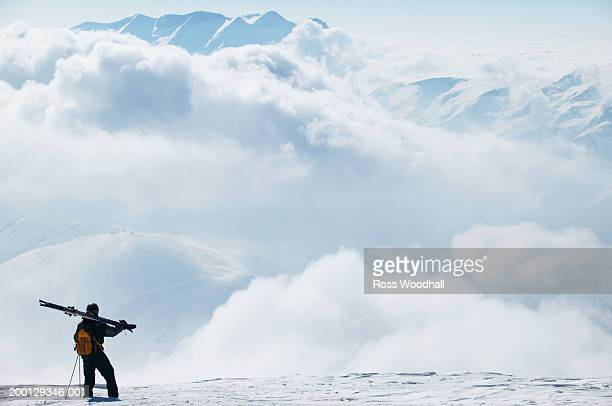 Man in skiwear looking at clouds over mountains, rear view