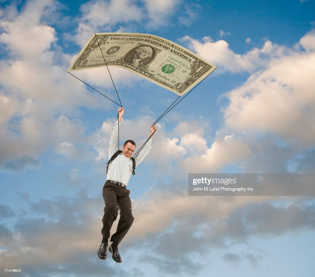 Man in sky with dollar bill parachute : Stock Photo