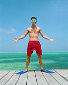 Man in snorkeling gear standing on ocean pier
