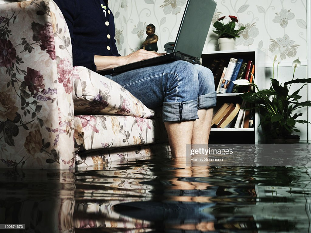 man in sofa in flooded room : Stock Photo