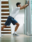 Man in sports clothes performing stretch, pushing against door frame