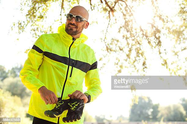 Man in sports wear sitting holding shoes