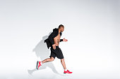 side view of young african american man in sportswear running on grey