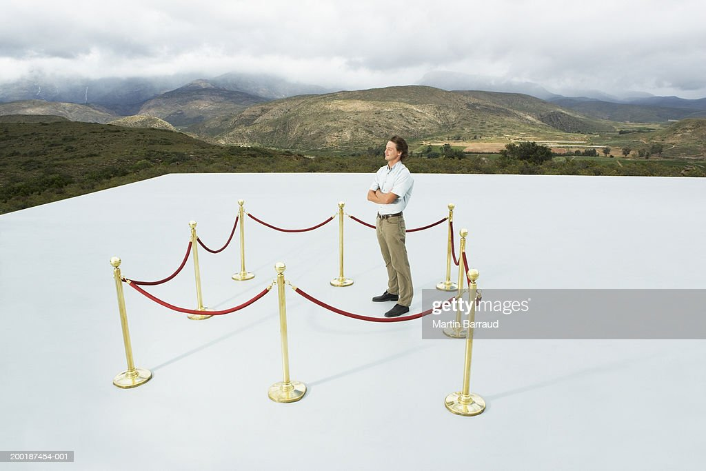 Man in square roped off area on platform, arms folded, outdoors : Stock Photo