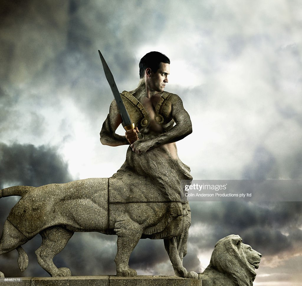 Man in statue of lion holding sword : Stock Photo